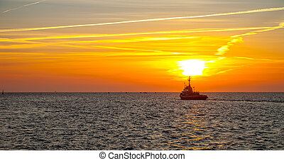 Tugboat on sea in the rays of the setting sun