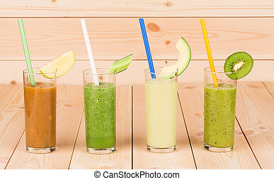 Natural fruit juices in glasses on the wooden background