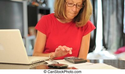 woman uses calculator and writes down info - Woman using a...