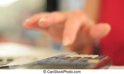 hand using calculator extreme close up - Woman using a...