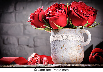 Valentine's setting with bouquet of red roses in vintage mug