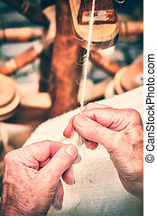 Hands of a woman making traditional wool spinning. Closeup...