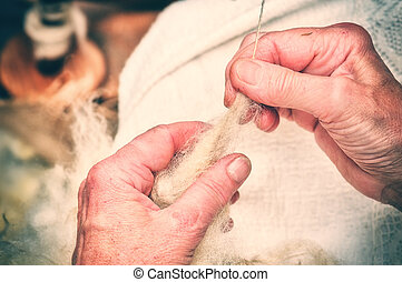 Hands of an old woman making traditional wool spinning...