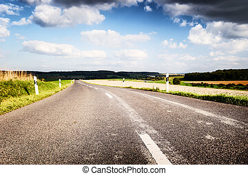 Summer road with cloudy sky