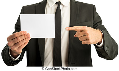 Businessman pointing to a blank card - Businessman in a suit...