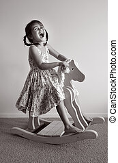 Wooden Rocking Horse - Happy girl age 04 ride on a wooden...