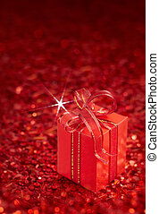 christmas gift - gift box tied with ribbon on red background