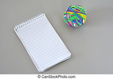 Note Pad with Rubber Band Ball on on office desk. concept...