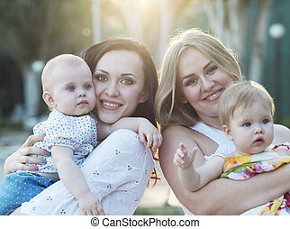 Two mothers and their babies - Two happy mothers and their...
