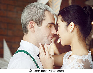 Cheerful married couple near the brick wall decorated with...