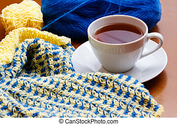 Cup of tea and knitting on wooden background