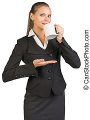 Businesswoman holding mug at her mouth and something on her...