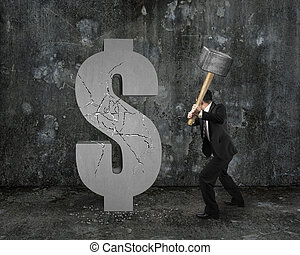 businessman holding hammer hitting cracked dollar sign with...