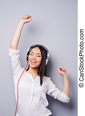 Happy music lover. Beautiful young Asian in headphones keeping eyes closed and arms raised while standing against grey background