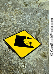 Falling Rock Sign - Danger falling rock sign on a cliff wall...