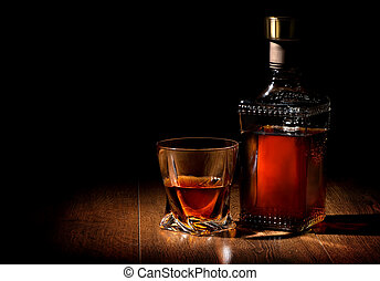 Whiskey on table - Bottle and glass of whiskey on a wooden...