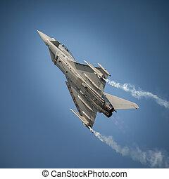 Jet fighter in flight,climbing in blue sky.