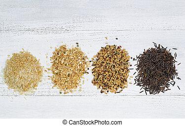 Varieties of Rice in piles on top of White Wood - Top view...