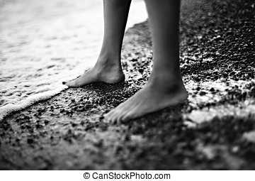 Feet in seawater - Female feet in the cold sea water black...