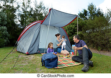 Family camping in a tent outdoors - Young family, father and...
