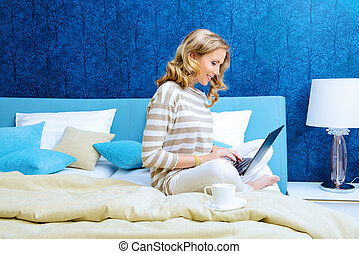 bedspread - Smiling elegant woman sitting on a bed with her...