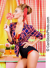 lady and lollipop - Pretty pin-up girl posing on a pink...