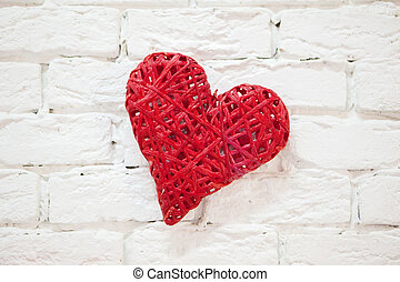 Red heart, handmade, hanging on a white wall