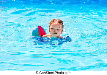 Baby girl swimming in pool with floats sleeves