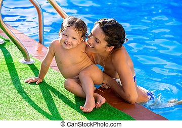 Happy mother and baby daughter swimming pool