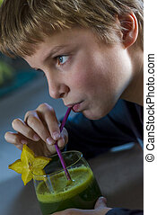 boy drinking green smoothie - boy with a glass of healthy...