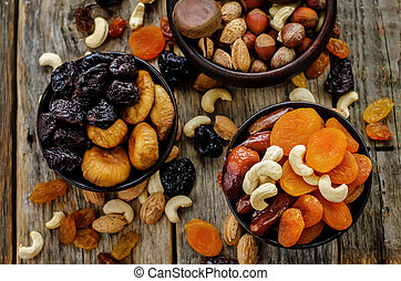 mix of dried fruits and nuts on a dark wood background....