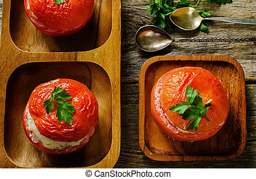 baked tomatoes stuffed fish on a dark wood background....