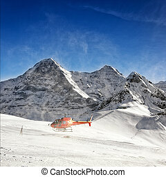 Red helicopter raising snow powder at take-off from alpine...