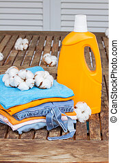 orange bottle of detergent and cotton clothes