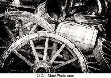 Old wooden barrels and broken wheels in retro setting