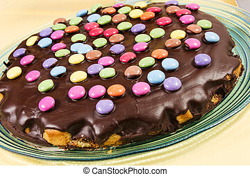 chocolate cake with smarties on the yallow tablecloth
