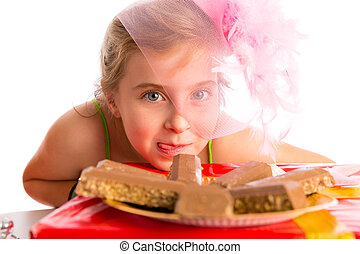 Hungry gesture blond kid girl in party chocolates