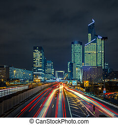 Night road with skyscrapers of La Defense, Paris, France -...