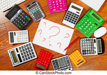 Question mark and calculators lying on the wooden flooring