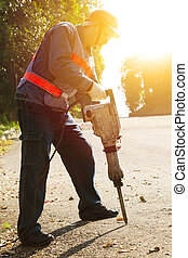 worker with pneumatic hammer drill equipment ready to...