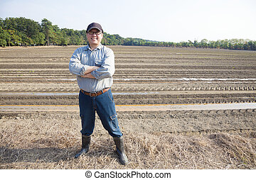 asian Farmer  standing on farming land