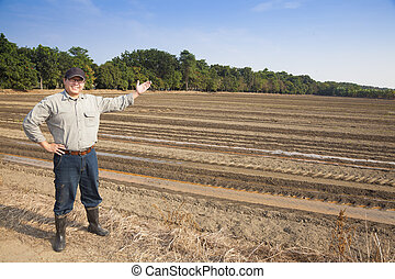Farmer man showing his farming land