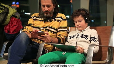 Father and son waiting - Father and son using digital tablet...