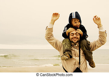 Happy Couple - smiling little boy riding on his fathers...