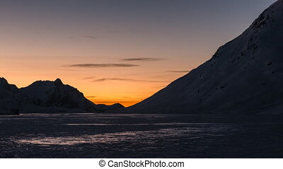 sunrise over a glacier lake - sun rising over a mountain...