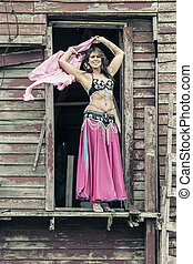 Woman in Doorway - A young beautiful woman in a pink and...