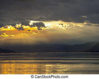Sun Poking Through The Clouds on Mountain Lake