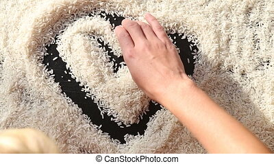 man hand draw heart on surface of rice