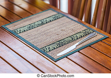 Place mat - an ornated place mat in a thai restaurant with a...