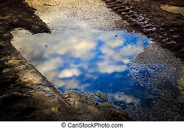Puddle reflection - Reflection of blue sky and White Clouds...